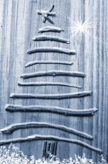 Christmas tree arranged from sticks on wooden snowy grey background