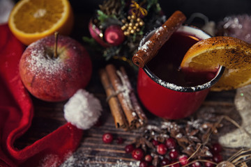 red cup of hot mulled wine in winter new year decoration