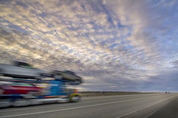 Sunset colors over interstart with eighteen wheeler