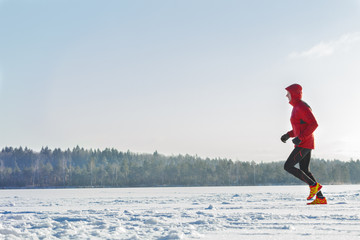 Trail racing runner wearing red protective sportswear on winter training session outdoors
