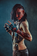 Zombie woman with the blood on the face and hands.