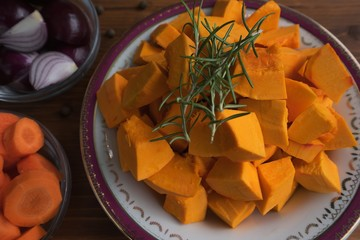 Food ingredients for cooking of traditional creamy pumpkin soup consist from chopped hokkaido pumpkin with fresh green rosemary sticks, red onion chopped in quaters and red carrot chopped to rings.