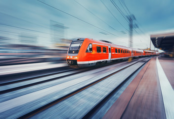 Modern high speed red passenger commuter train in motion at the railway platform. Railway station. Railroad with motion blur effect. Industrial concept landscape with instagram toning. Transportation