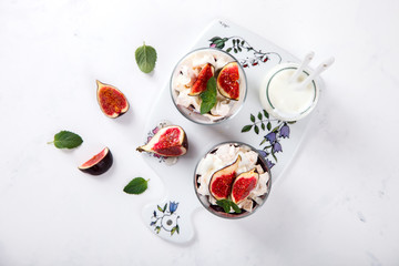 Eton Mess. Fresh figs with whipped cream and meringue in a glass beaker. Dessert.Meringue from egg whites. selective focus