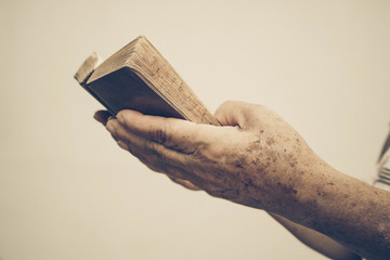 Old female hand holding an old small book of bible