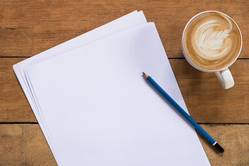 Office desk table with blank paper page, pencil and cup of coffee.Top view with copy space.Office supplies and gadgets concept.