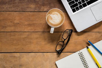 Office desk table with blank paper page, pencil, pen, glasses, laptop and cup of coffee.Top view with copy space.Office supplies and gadgets concept.