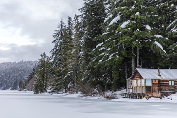 Fotomurales - Winter at Whistler British Columbia, Canada. Winter wonderland in the Pacific North West. Winter cabin covered in snow with forest and mountain background.