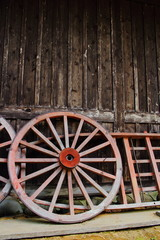 Wooden wheels leaning onto wooden house