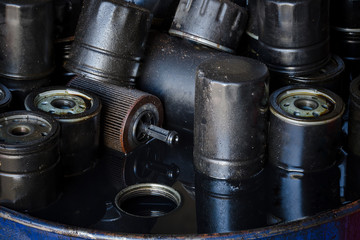 Picture of motor oil as product of oil refining industry. Era of internal combustion engines coming to end. Closeup picture of old oil filters for automobile.