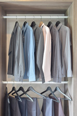 row of colorful shirts and pants hanging  in wooden wardrobe