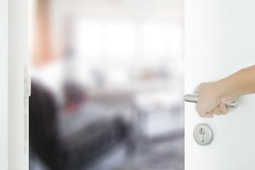 man hand opening white door to living room modern style interior