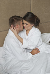 happy woman looking at husband while lying in bed