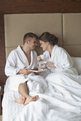 Beautiful young couple having breakfast in bed.