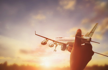 close up photo of man's hand holding toy airplane and sunset background
