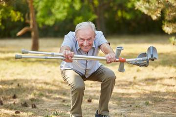 Senior macht Kniebeuge mit Krücken