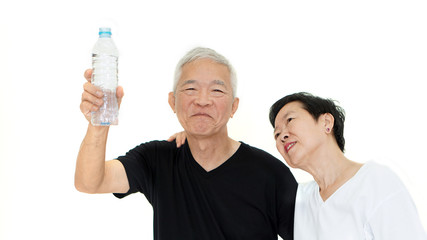 Asian Senior couple holding water bottle stay dydrate for health