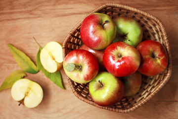 fresh apples in a basket on a wooden table