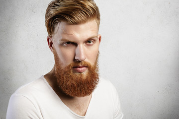 Close-up portrait of young Caucasian man with long ginger beard and trendy hairstyle. Young hipster gives an inquiring look with one raised eyebrow. His skin is perfect and expression is reserved.