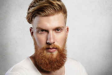 Portrait of young bearded dandy with hair brushed back in a trendy manner. Attractive Caucasian man in white T-shirt looking ahead, his charming green eyes sparkling. Indoors shot in white studio.