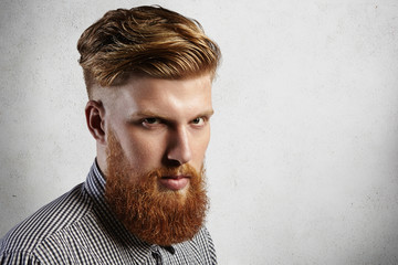 Manful European hipster in checked shirt looking seriously at the camera. His stylish haircut and well-trimmed blond beard say that he is loyal client of barbershop and takes care of his appearance.