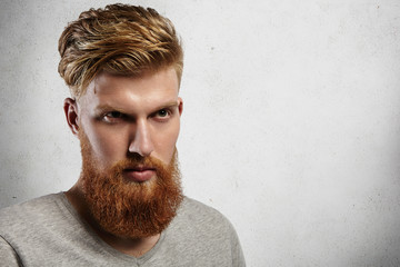 Portrait of young European hipster with fair skin and trendy ginger beard. Fashionable undercut hairstyle and handsome face features together with virile character make him look utterly attractive.