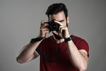 Young male photographer taking picture with digital slr camera white focusing lens over gray studio background