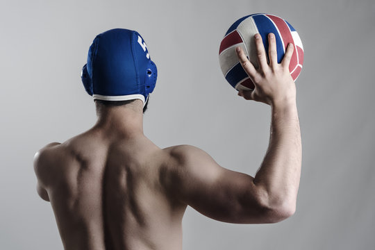 Back view of muscular water polo player holding and shooting ball. Desaturated gritty portrait over gray background.