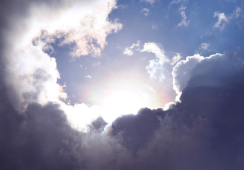 Amazing sky and cloudscape as the sun emerges among dramatic clouds. Symbol for a new day full of hope and possibilities.