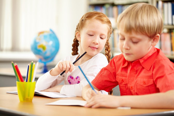 A blond boy and a red haired girl sitting at table and drawing