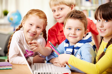 Four smiling schoolchildren sitting in classroom with a laptop, looking at camera and smiling