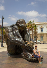 Woman traveler sitting on memorial sculpture at Cartagena Spain located in public port promenade