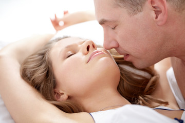Close-up of a man kissing his girlfriend lying in bed