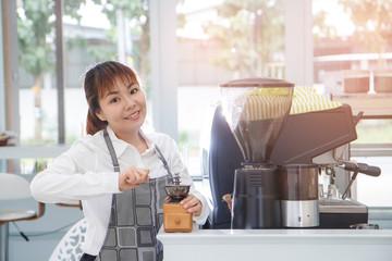 Beautiful Asian woman coffee barista using coffee machine in cou