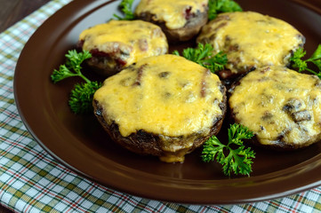 Stuffed mushrooms with salami and mozzarella cheese in a clay bowl on a wooden background. Close up