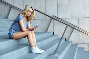 Young blonde girl with beautiful smile posing while sitting with mobile phone in hands on shopping center stairs, gorgeous cheerful female in casual outfit working with her cell during rest in mall
