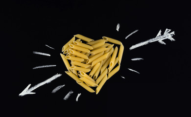 Heart shape made of  penne pasta. Pasta in the shape of a heart on a black background. I love pasta.