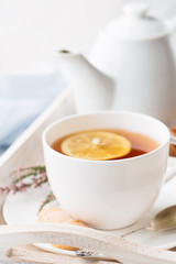 Tray with cup of hot black tea, lemon and honey
