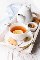 Tray with cup of hot black tea, lemon and honey, selective focus