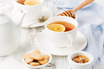 Cups of hot black tea, lemon and honey on white rustic wooden background. Breakfast concept. Selective focus