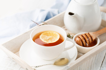 Tray with cup of hot black tea, lemon and honey on white rustic wooden background. Breakfast concept. Selective focus