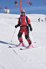 Young woman skiing downhill with blue sky and chairlift in the background