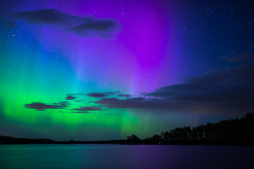 Wall Mural - Scenic view of northern lights over calm lake