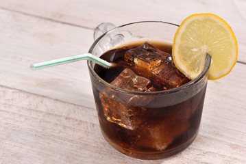 Cola drink with ice cube, lemon slice and straw on white rustic wood background