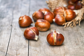 Roasted sweet chestnuts on grey rustic wooden table. Copy space