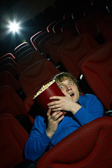 Young man watching thriller at cinema hall and hiding behind popcorn bucket