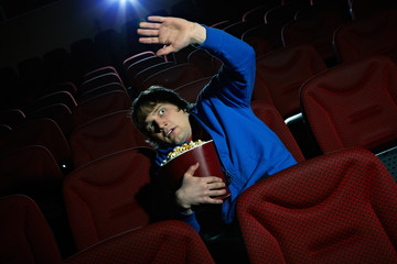 Young man is terrified by the scene seen on the screen in cinema hall