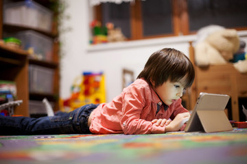 Cute little boy, lying on the floor in kids room, playing on tab