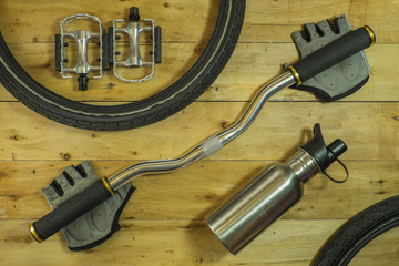 Overhead view of bicycle bicycle handlebars on a rustic wooden floor.