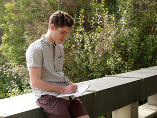 Young man outdoors, writing notes in notepad
